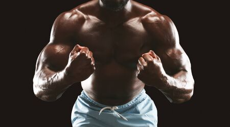 Sexy muscular man body over black studio background, cropped