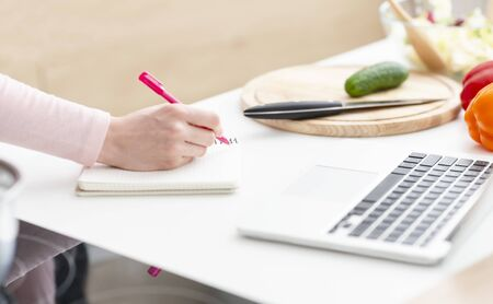 Creating content. Millennial woman life or business coach writing down thoughts in copybook and working on laptop, closeup