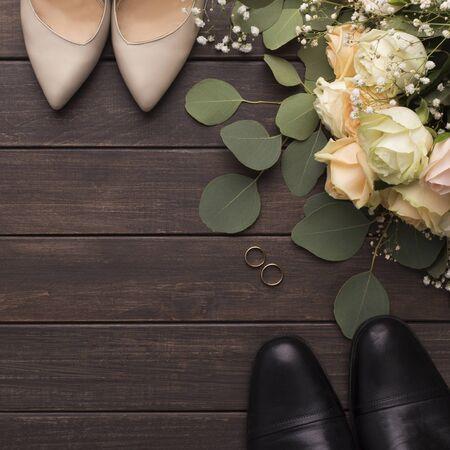 Braut Bräutigam Schuhe und Hochzeit kleiner Rosenstrauß auf Holzuntergrund mit Kopierraum