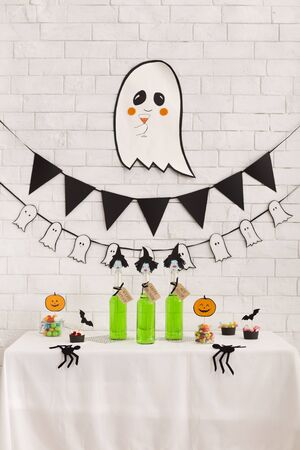 Creative halloween concept with cute ghost above table with green ugly drinks, vertical panorama Stock Photo