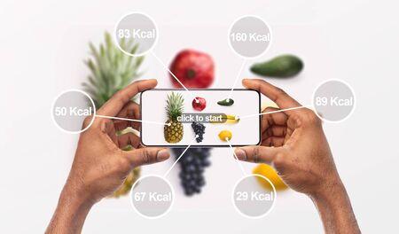 Mujer sosteniendo teléfono móvil con aplicación que cuenta calorías por foto, fondo, panorama