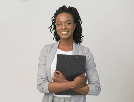 African American Business Lady Holding Folder Smiling At Camera Over Gray Background. Office Work Job. Studio Shot