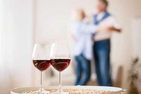 Celebrate anniversary. Mature couple in love dancing on background, glasses with red wine on foreground Standard-Bild - 130405438