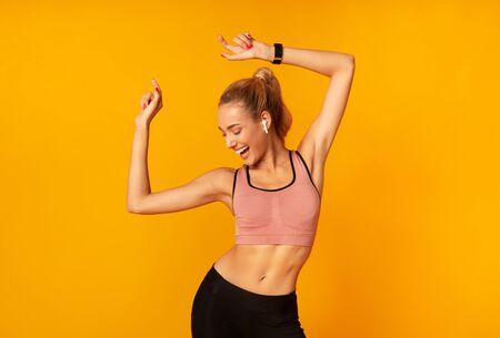 Sportliche Frau in drahtlosen Kopfhörern, die Musik über gelben Studiohintergrund tanzen. Freiraum