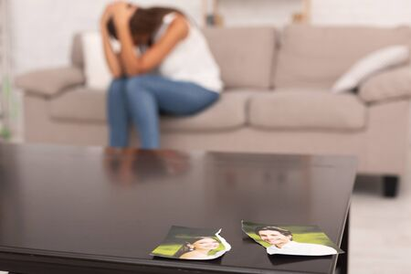 Breakup. Torn Photo Of Happy Couple Lying On Table While Unrecognizable Depressed Girl Crying Sitting On Couch Indoor. Stock Photo