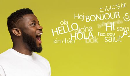 Courses concept. Young millennial afro man saying hello in many languages on yellow background