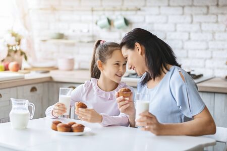 Mother and daughter eating cupcakes and drinking milk, spending time together in kitchen. 写真素材