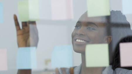 Smiling Black Female Entrepreneur Putting Sticky Notes On Glass Board In Modern Office. Business Planning. Panorama