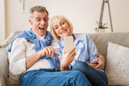 Modern grandparents. Excited senior couple making video call on smartphone, free space