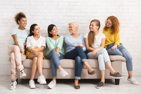 Multiethnic Women Looking At Each Other Sitting On Sofa Against White Wall Indoor. Diversity And Equality Concept