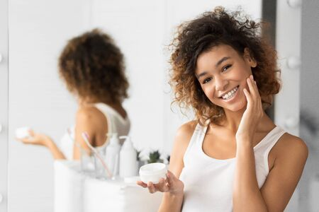 Cheerful Afro Girl Using Face Cream Touching Perfect Skin Standing Next To Mirror In Bathroom. Cosmetic Product. Selective Focus