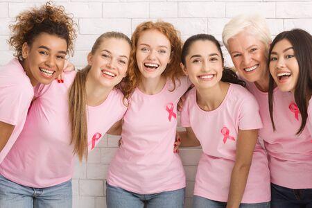 Diverse vrouwen In T-Shirts met roze borstkanker linten lachen om Camera knuffelen staande op een witte achtergrond. Stockfoto