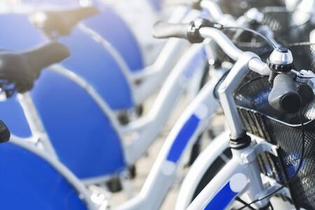 Rent-a-bike service. Similar blue bicycles for sharing, close up Фото со стока