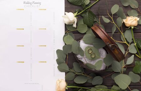 Wedding rings and paper planning checklist on wooden table with green natural leaves, panorama Reklamní fotografie