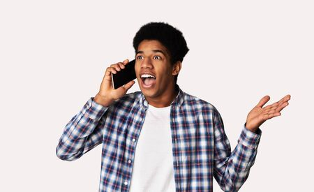 Emotional african-american guy talking on cellphone, shocked by news, white background Stockfoto