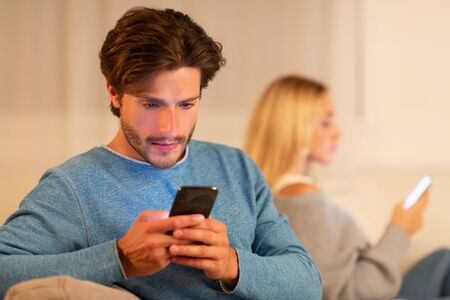 Infidelity. Cheating Husband Chatting On Mobile Phone Sitting Next To Wife On Sofa At Home. Selective Focus