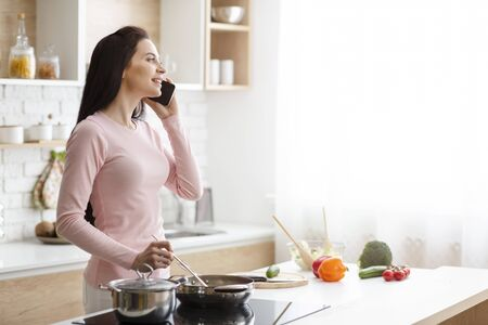 Always in touch. Millennial woman talking on phone, preparing lunch at kitchen, free space