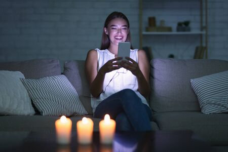 Happy Girl Texting On Cellphone Waiting For Boyfriend Sitting On Sofa In Dark Room Lit By Candles. Selective Focus