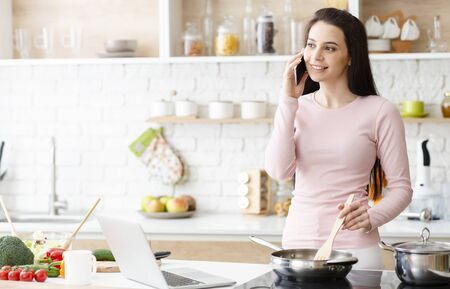 Online consultation. Young woman cooking and talking on cellphone at kitchen, free space