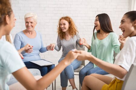 Group Therapy. Smiling Diverse Women Sitting In Circle Holding Hands Indoor. Selective Focus Stock Photo