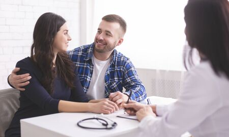 Good test results. Young couple smiling at each other, happy to hear doctors news at appointment in clinic Stock Photo
