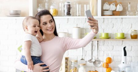 Smile. Happy mother with baby photographing themselves on cellphone at kitchen, panorama with empty space Stock Photo - 130627931