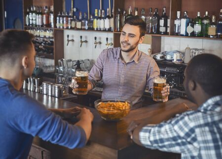 Handsome bartender serving two guys, giving them glasses with beer Фото со стока