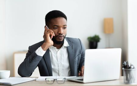 Focused african american businessman talking on cellphone and working on laptop in modern office, panorama with copy space
