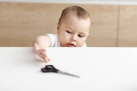 Caution at home. Baby boy trying to get scissors from kitchen table, free space Stock Photo