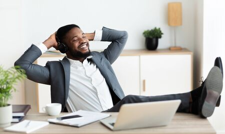 Dont worry be happy. Handsome black businessman in headphones listening his favorite music at workplace in modern office, panorama