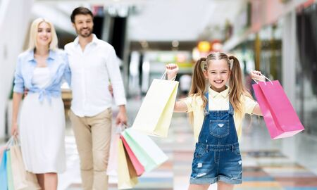Young Parents And Excited Little Daughter Carrying Shopping Bags Walking Together In Mall Buying Seasonal Updates. Selective Focus 版權商用圖片