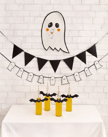 Children party. Cute paper ghost and yellow drinks for kids party over white bricks wall background