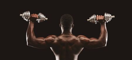 Back view of african american male fitness model pushing dumbbells up, black studio background, panorama Reklamní fotografie