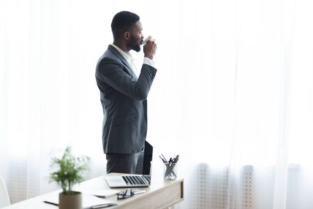 African businessman drinking coffee and enjoying city view from window in office, copy space Reklamní fotografie