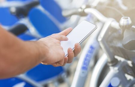 Rental transportation app. Man reserving bicycle with mobile application online, close up Banco de Imagens