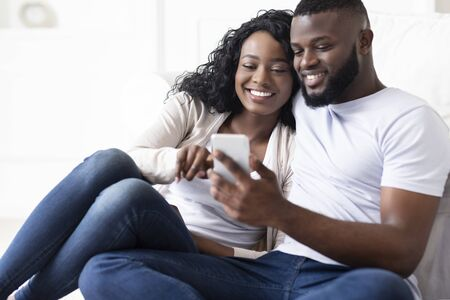 Cheerful african american husband and wife scrolling photos in smartphone together sitting at home
