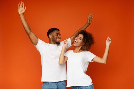 Positive african american man and woman dancing and laughing on orange studio background Stock Photo
