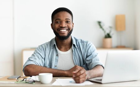 Employee of the month. Positive black guy posing to camera at workplace