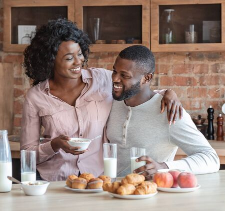 African young married couple having breakfast together at kitchen, woman sitting on man lap and hugging him, drinking milk and eating pastry, copy space