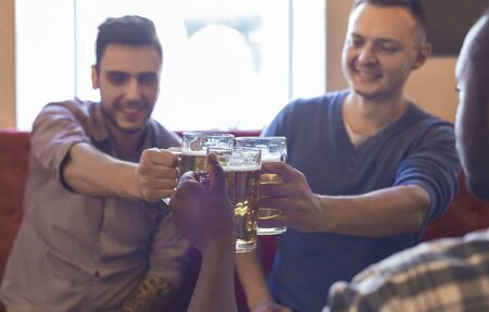 Happy multiracial young mates clinking glasses with beer together, spending time at pub, free space
