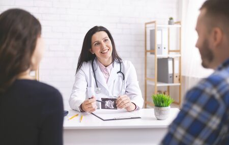 Friendly doctor explaining pregnancy diagnosis with ultrasound picture to young couple at clinic Stock Photo