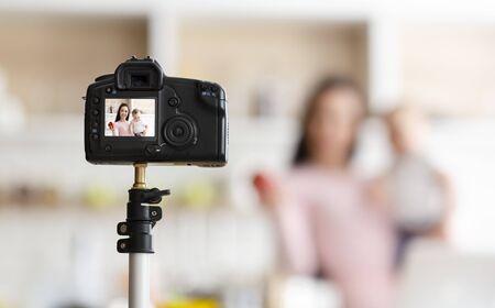 Online cursussen babyvoeding. Moeder met peuter die video opneemt voor webinar, keukeninterieur, lege ruimte Stockfoto