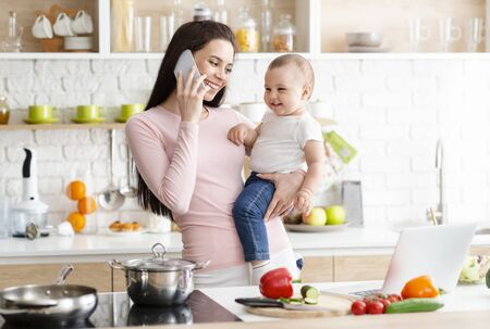 Pleasant talk. Young mother talking on phone, holding her baby at kitchen, free space
