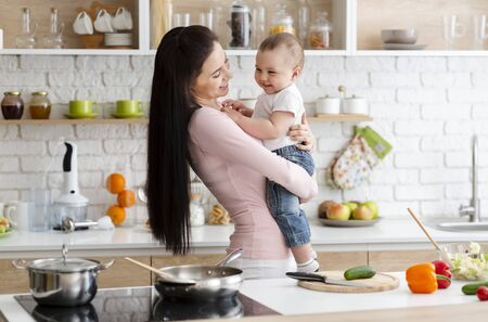 Kitchen fun. Little baby laughing on mother hands, cooking lunch together, free space Stock Photo