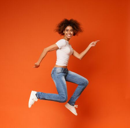 Going crazy. Funny portrait on young african american woman in humorous jump on orange background