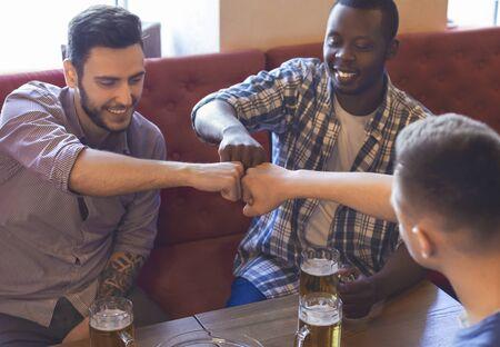 Brotherhood concept. Three mixed race mates bumping fists together, drinking beer at bar Фото со стока