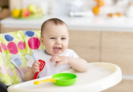 Little chef. Cheerful baby boy playing with toy pan and cooking spatula, free space Stock Photo - 130628143