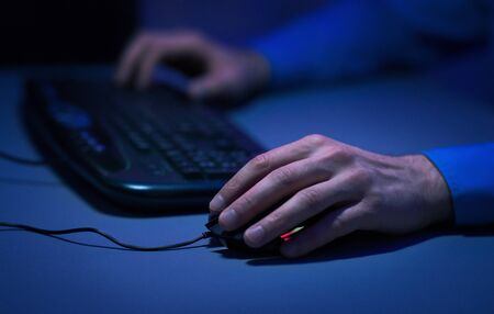 Male hands on computer keyboard and mouse, man surfing internet late at night