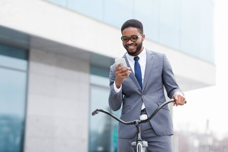 Excited businessman using phone against office building, come to work by bike, free space