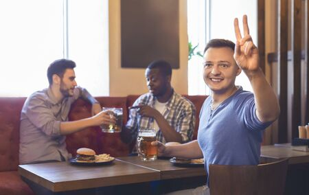 Excited young cheerful guy ordering more drinks, resting with friends at bar, panorama with copy space